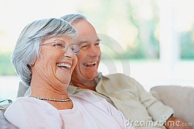 A happy senior couple watching television