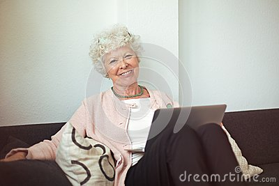 Happy Senior Lady at Home with Laptop