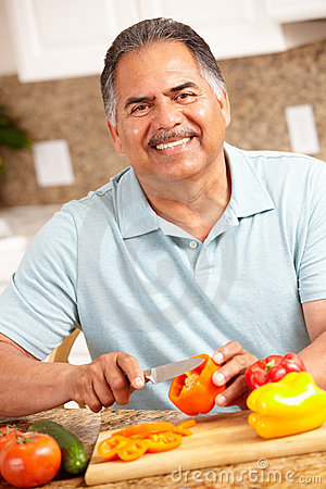 Happy senior man chopping vegetables