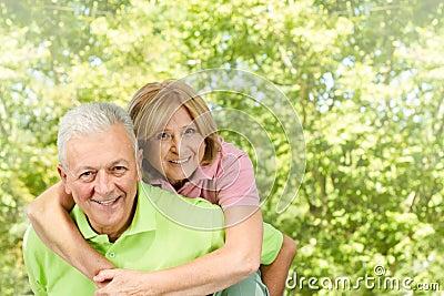 Happy senior man giving piggyback