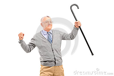 Happy senior man holding a cane and gesturing happiness