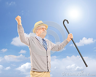 Happy senior man holding a cane and gesturing happiness outside