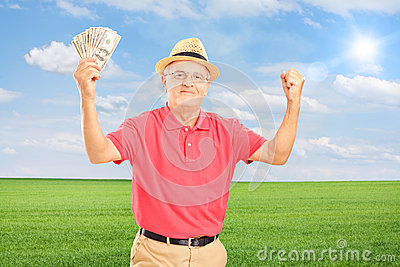 Happy senior man holding money and gesturing happiness on a fiel