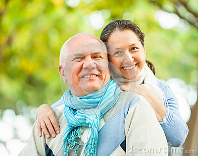 Happy senior man and mature woman against forest