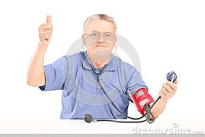 Happy senior man measuring blood pressure and giving a thumb up