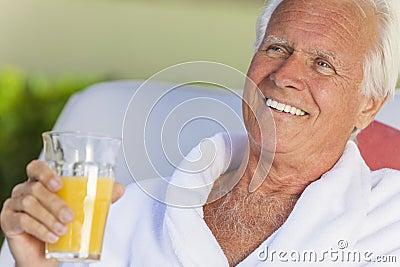 Senior Man In Bathrobe Drinking Orange Juice
