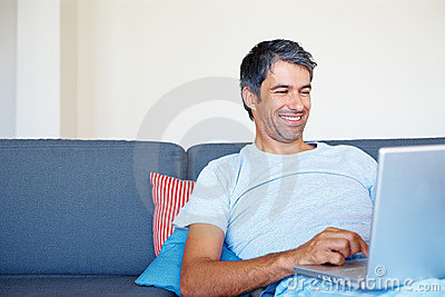 Happy senior man surfing his laptop at home