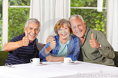 Happy senior people holding thumbs