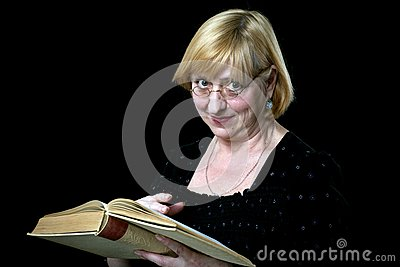 Happy senior woman with book and glasses on black