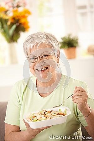 Happy senior woman eating salad