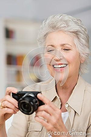 Happy senior woman setting her compact camera