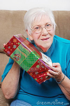 Happy senior woman shaking her christmas present