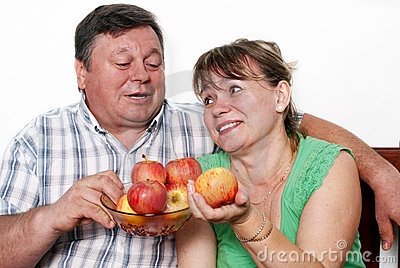 Happy seniors couple with apple