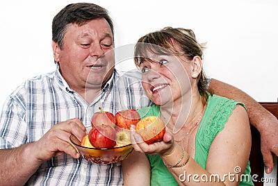 Happy seniors couple with apple