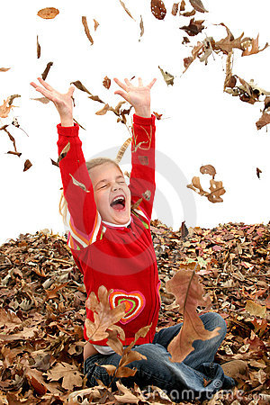 Happy Seven Year Old Girl Playing in Pile of Leaves