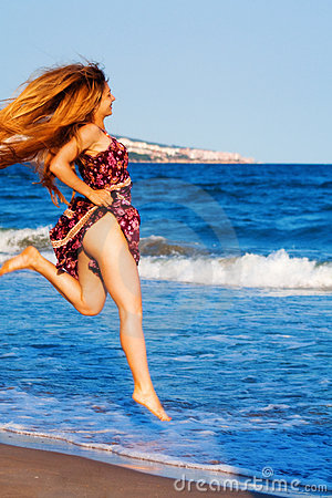 Happy sexy woman jumping on the beach