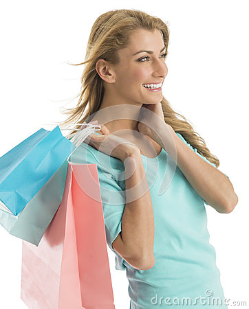 Happy Shopaholic Woman Looking Away While Carrying Shopping Bags