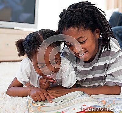 Happy siblings reading lying on the floor