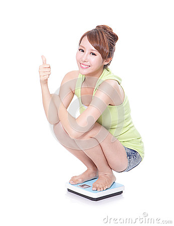 Happy slim woman with scales and show thumb up