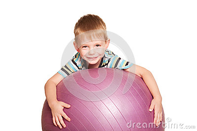 Happy small boy with the fitness ball.