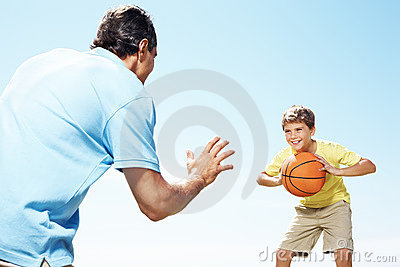 Happy small kid playing basketball with his father