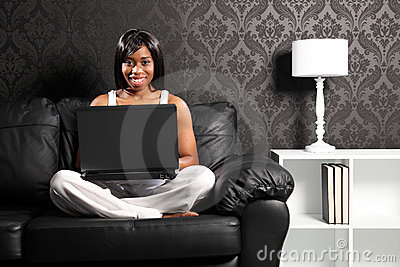 Happy smiling black woman on sofa surfing internet