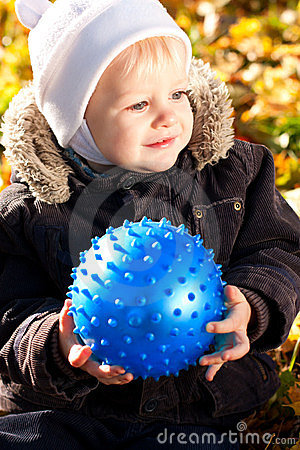 Happy smiling child with blue ball in his hands