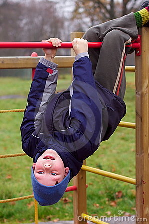 Happy smiling child in playground head down
