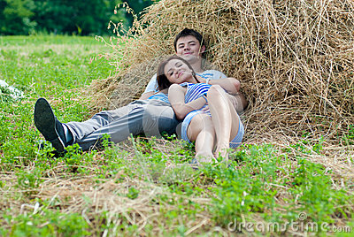 Happy smiling couple hugging on hay