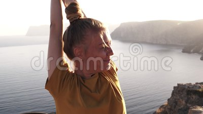 Happy, smiling female camper in yellow T shirt spreads her hands and welcomes morning sun. Waked up, standing on a hill. Against the morning sun light. Seaside stock footage