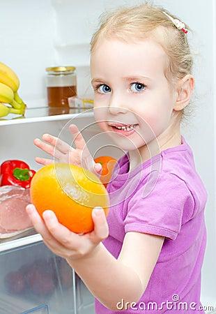 Happy smiling little girl holding orange