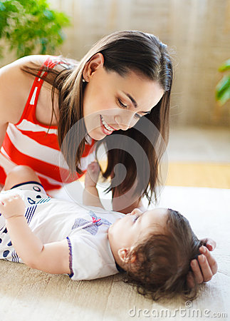 Smiling mother with eight month old baby girl indoor