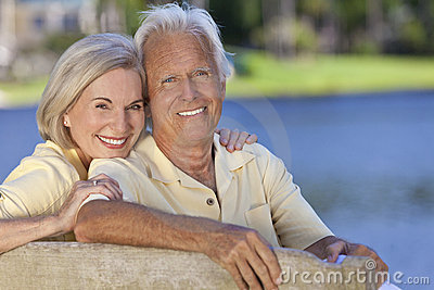Happy Smiling Senior Couple Sitting On Park Bench