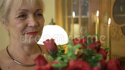Happy smiling woman holding a large bouquet of red roses. Birthday, Mothers Day, anniversary or Valentines. Middle-aged man giving woman bouquet of red roses