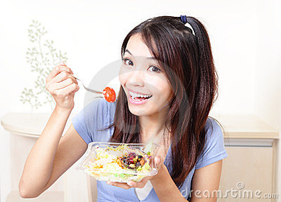 Happy smiling woman with salad at home