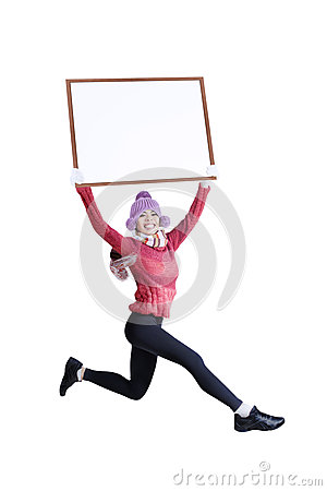 Happy smiling woman in winter clothing holding blank board - isolated