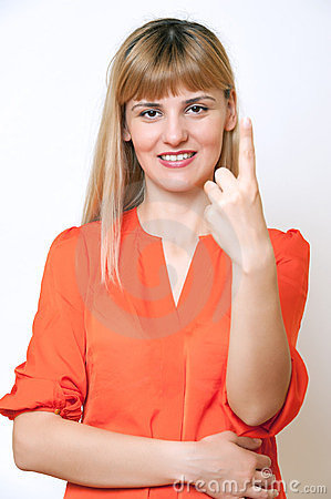 Happy smiling young business woman showing one finger.