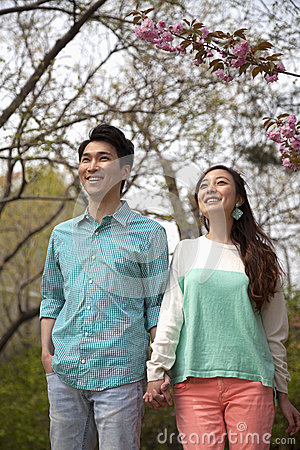 Happy smiling young couple holding hands in the park in springtime, three quarter length