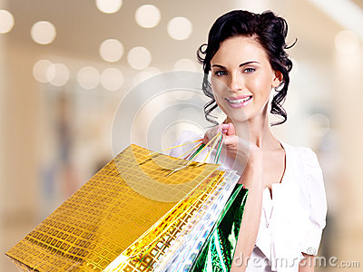 Happy smiling young woman with color bags.
