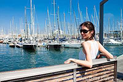 Happy smiling young woman in a sea port