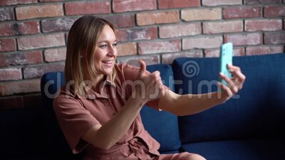 Happy smiling young woman talking video chat using mobile phone. Happy smiling young woman talking video chat using mobile phone and showing thumbs up gesture stock video footage