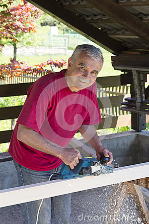 Happy smilling carpenter with power plane tool