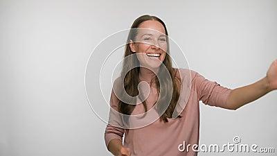 Happy sorglos lächelnde Brunette Frau in rosa Bluse tanzen über weißem Hintergrund stock footage