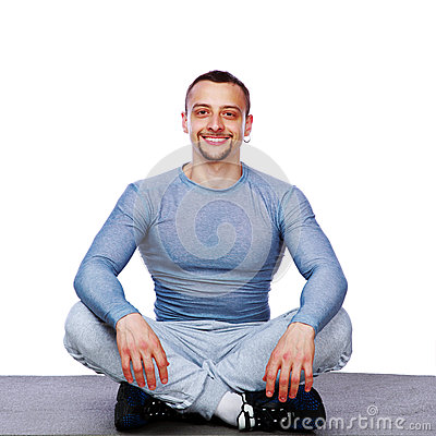 Happy sportsman sitting in the lotus position