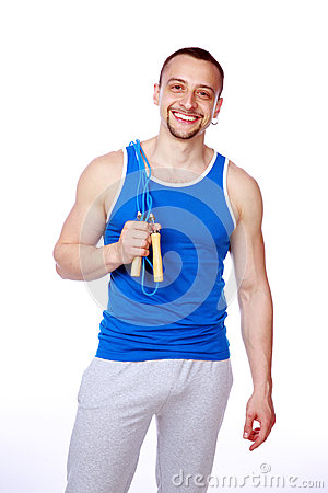 Happy sportsman standing with jumping rope