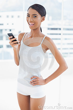 Happy sporty model using her smartphone