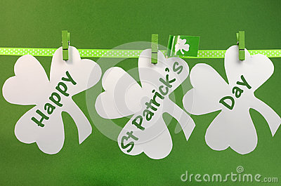 Happy St Patricks Day message greeting written across white shamrocks hanging from pegs on a line