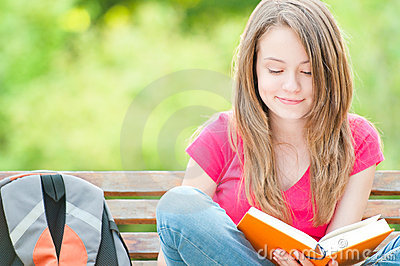 Happy student girl sitting on bench with book