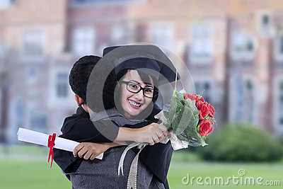 Happy student hugging boyfriend on graduation at school