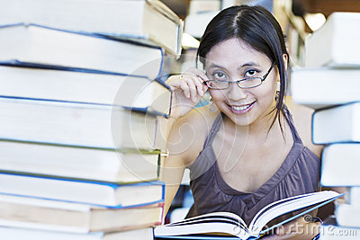 Happy student reading books in library